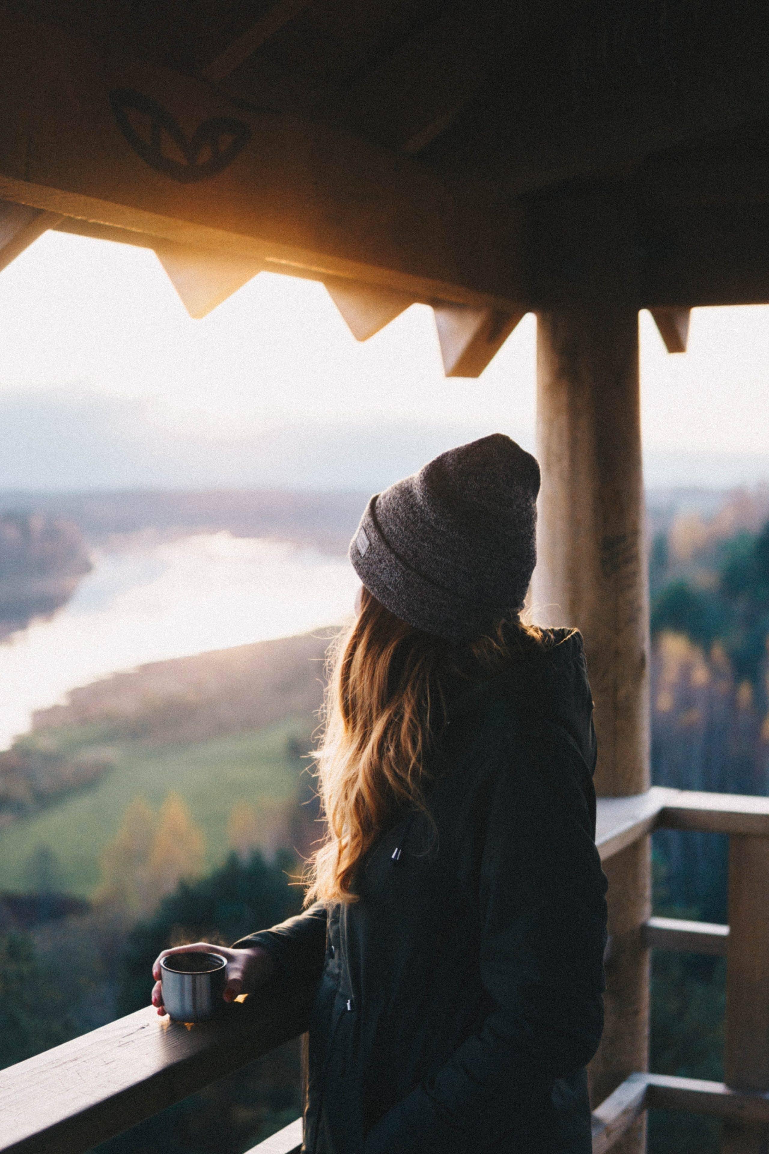 Jeune femme sur le balcon d'un hôtel en train de profiter de la vue sur les montagnes